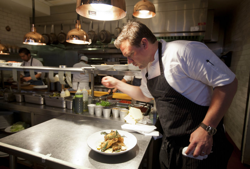 Tyler Florence puts a finishing touch on his fried chicken dish in the kitchen.