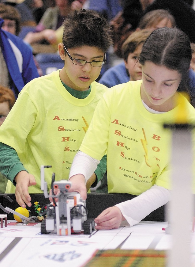 Alex Millones, left, and Abigail Bloom set up their team's robot to compete Saturday at the Maine FIRST Lego League Championship at the Augusta Civic Center.