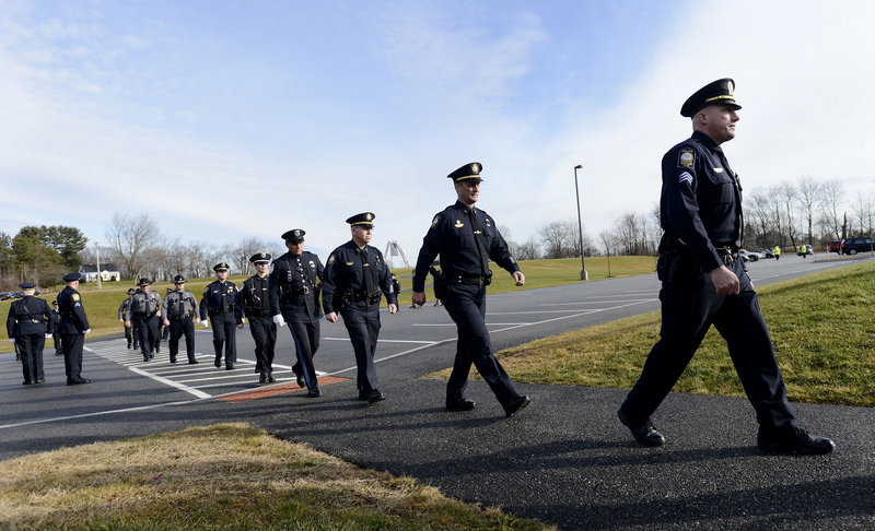 Police officers arrive at a memorial service for Peter MacVane, a popular South Portland police officer, Sunday at the Westbrook Performing Arts Center. MacVane, 61, a 34-year veteran of the department, died Wednesday after a five-year battle with cancer.