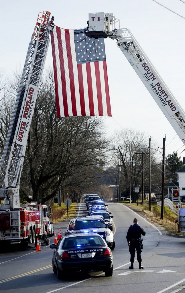 """A police procession arrives Sunday at the Westbrook Performing Arts Center for MacVane's memorial service. """"Even on his worst days he continued to give us some of our best days,"""" said South Portland Police Chief Edward Googins."""