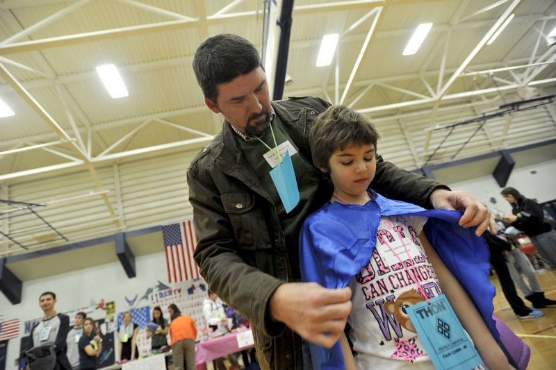 Tom Whitehead and daughter Emily attend the Thon Carnival last week in University Park, Pa. Emily became the first child to have her own cells genetically engineered to recognize and attack the cancer cells in her body.