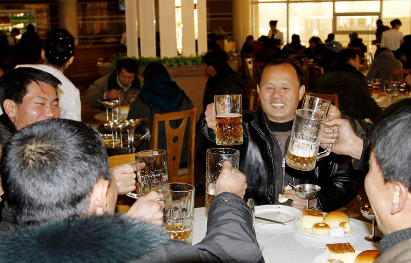 North Koreans toast with beer Wednesday at a Pyongyang diner after hearing news of the long-range rocket launch that is part of a quest to develop the technology needed to deliver a nuclear warhead.