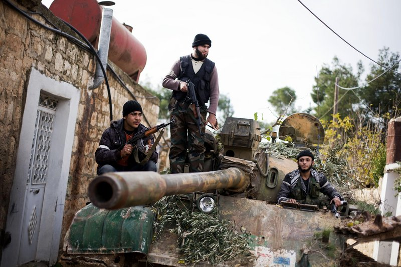 Kurdish members of the Free Syrian Army command a tank stolen from the Syrian Army in Fafeen village, north of Aleppo province in Syria, Wednesday.