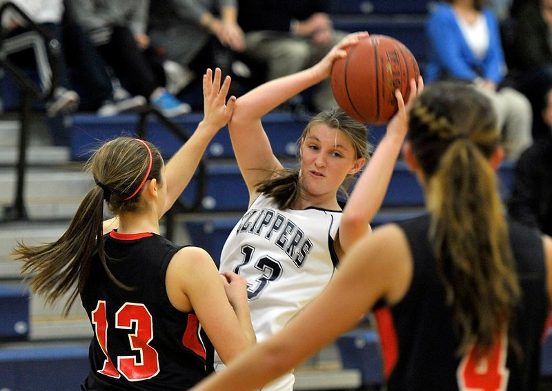Monica Austin of Yarmouth looks for an open teammate Thursday night while guarded by Nicole Moody, left, and Sydney Lachapelle of Wells during their Western Maine Conference game at Yarmouth. Wells came away with a 51-47 victory.