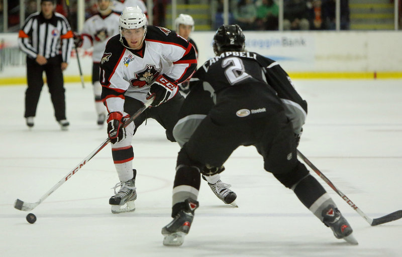 Chris Brown of the Pirates moves the puck down the ice as Manchester's Andrew Campbell defends Friday during a 4-2 win by the Pirates at the Colisee in Lewiston.