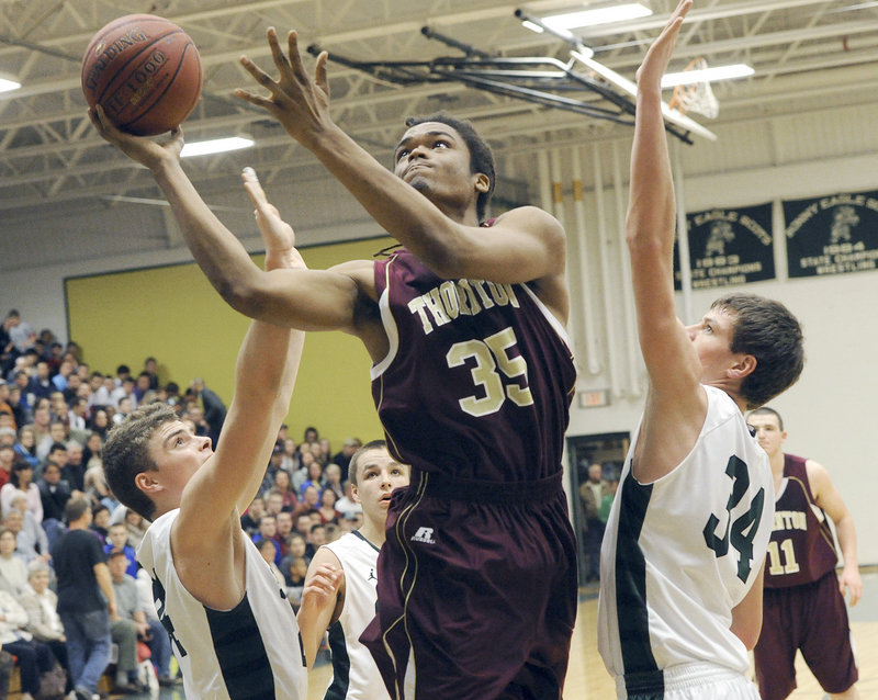 Malcolm Dopwell of Thornton finds room for a layup between Jon Thomas, left, and Kyle Wright of Bonny Eagle.