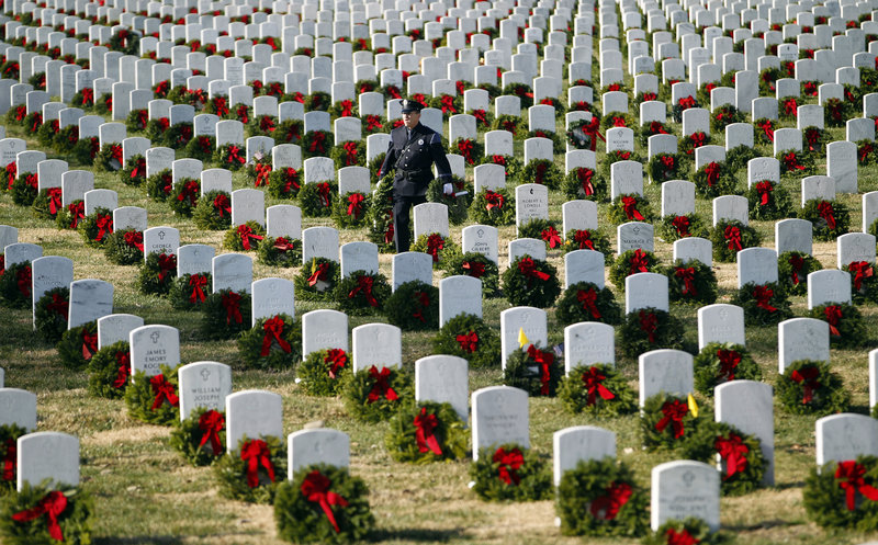 Portland police officer Terry Fitzgerald helps lay holiday wreaths at graves at Arlington National Cemetery on Saturday, or Wreaths Across America Day, an event that has expanded to all 50 states since it was started in 1992 by Maine businessman Morrill Worcester.