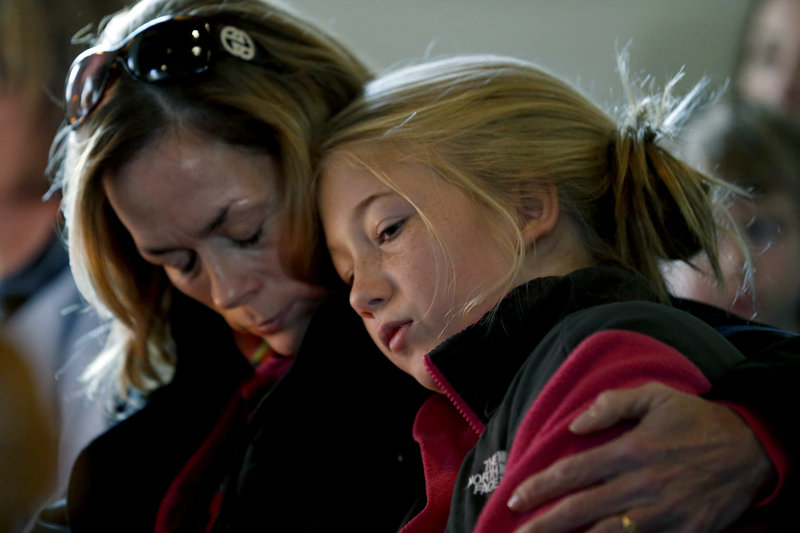 """Molly Delaney holds her 11-year-old daughter, Milly Delaney, during a service at St. John's Episcopal Church on Saturday in honor of the victims of Friday's shootings at Sandy Hook Elementary School in Newtown, Conn. The effect of the shooting rampage on this western Connecticut town was deep and painful. """"Our wound is deep because we are a close-knit community,"""" Patricia Llodra, the town's first selectman, told reporters. """"We truly care for each other."""