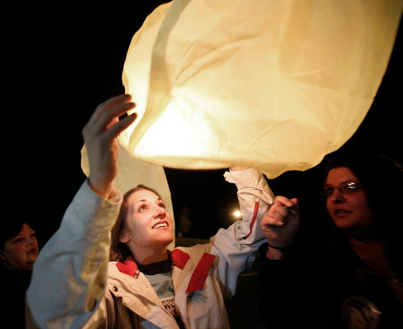 "Trista Reynolds, Ayla's mother, floats a lantern skyward during the Portland event Saturday. She says Justin DiPietro, Ayla's father, ""could end all of this within seconds if he would just be a father and actually speak for his daughter."""