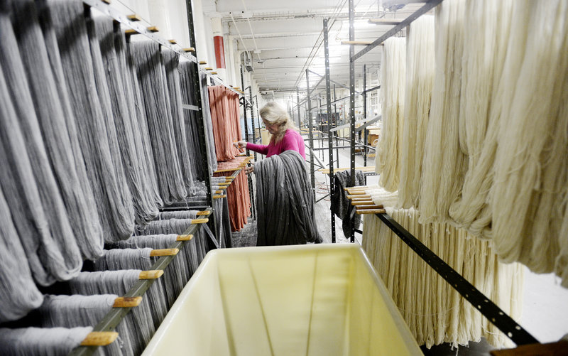 Noreen Mahoney hangs dyed yarn to dry at the Saco River Dyehouse in Biddeford on Thursday.