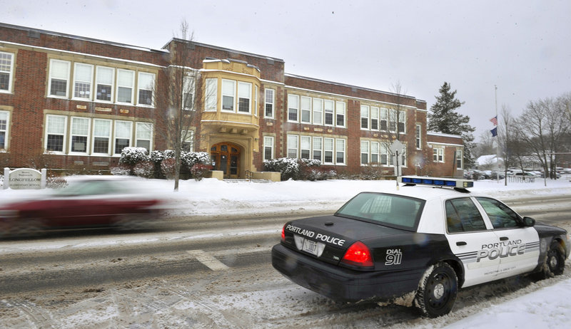 A Portland police cruiser sits Monday in front of Longfellow Elementary School on Stevens Avenue as police stepped up patrols of schools in the wake of the Newtown, Conn., shootings.