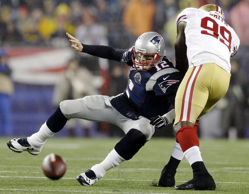 San Francisco's Aldon Smith forces an incomplete pass by Tom Brady during Sunday's game in Foxborough. The Patriots dropped to third in the AFC playoff race with a 41-34 loss.