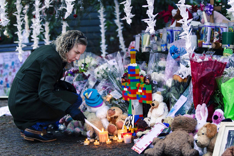A woman lights candles Monday in Newtown, Conn., while visiting a memorial to the victims of the recent shooting at Sandy Hook Elementary School.