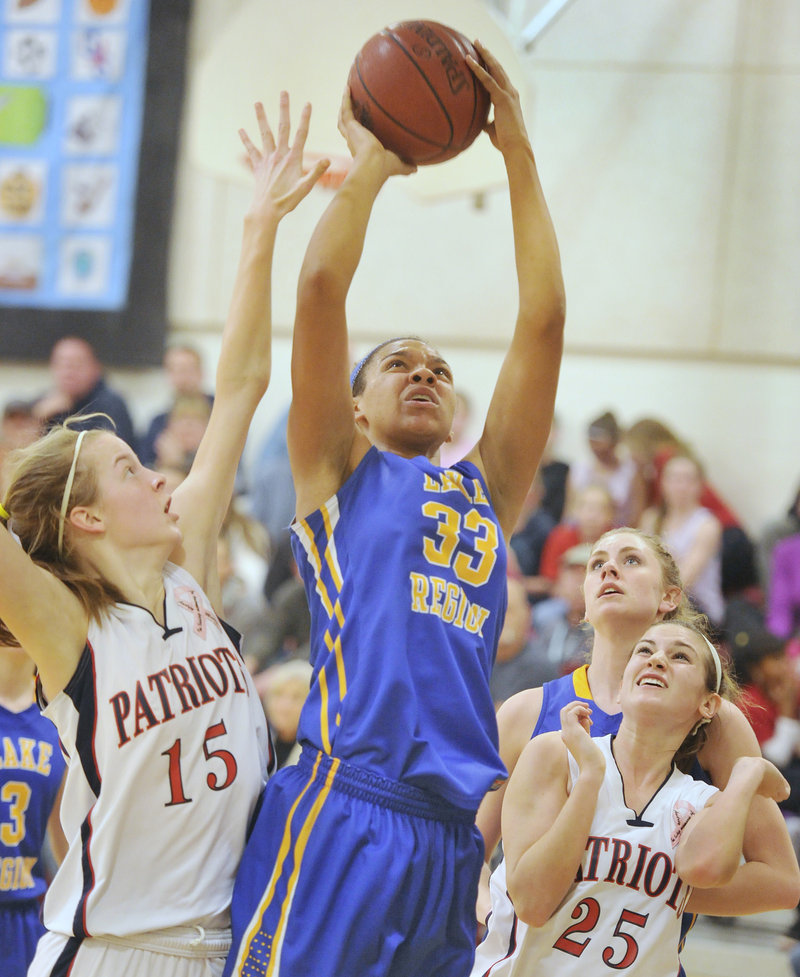 Tiana-Jo Carter of Lake Region goes up with a shot between Patriots defenders Stephanie Greaton, 15, and Haylee Cote Tuesday night in Gray. Carter scored 10 points in the Lakers' 47-41 win.