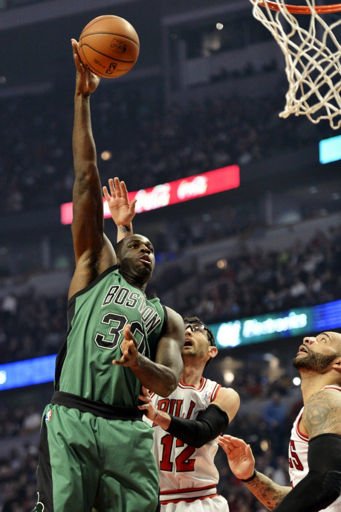 Brandon Bass of the Boston Celtics soars over Kirk Hinrich of the Chicago Bulls to get off a shot Tuesday night.