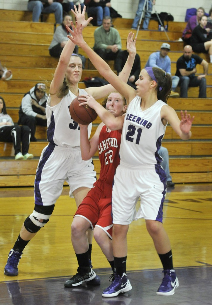Heather LeBlanc of Sanford can't find room to get off a shot while guarded by Deering's Marissa MacMillan, left, and Alexis Stephenson.