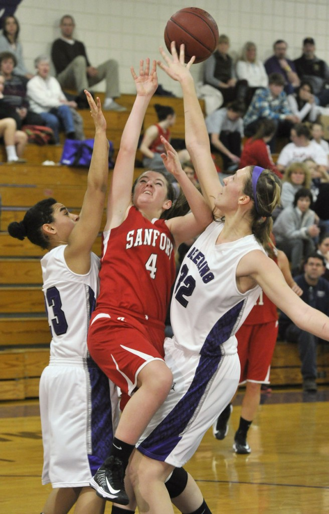 Morgan Fogg of Sanford gets fouled by Deering's Marissa MacMillan, right, while Keneisha DiRamio also defends during their SMAA girls' basketball game Thursday.