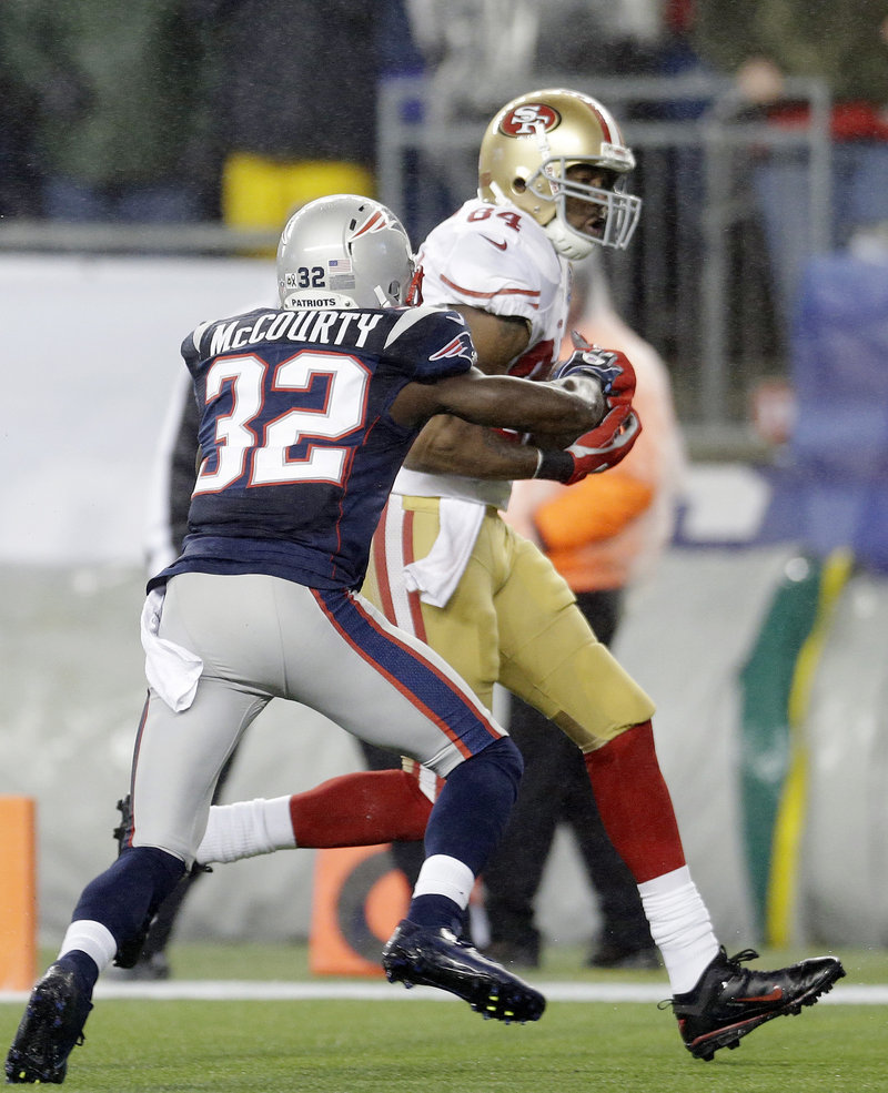Randy Moss scores against his former team after pulling in a first-quarter pass despite the efforts of safety Devin McCourty.