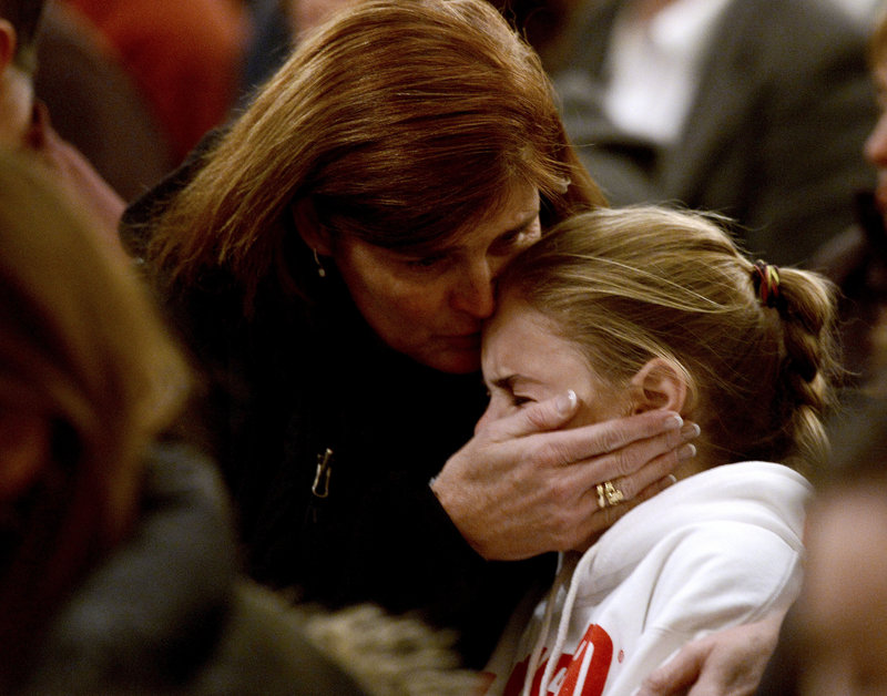 """A woman comforts a young girl during a vigil service last week in Newtown, Conn., for victims of the Sandy Hook Elementary shooting. Programs for children with mental and neurological disorders help students adjust to the world around them, but """"once they have finished public school, all assistance ends,"""" isolating at-risk young men, a reader says."""