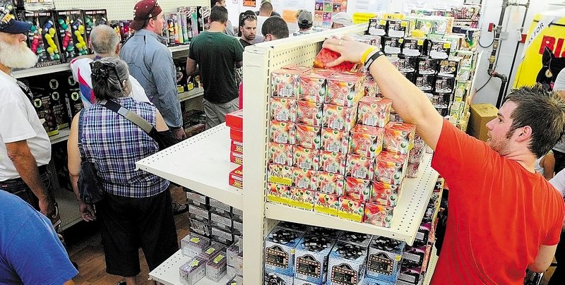 """Tyler Basinger restocks shelves as customers line up in July at the Pyro City fireworks store in Manchester. Owner Steve Marson said he plans to open two more stores in Maine next year. """"In my opinion, it was a very safe year,"""" he said."""