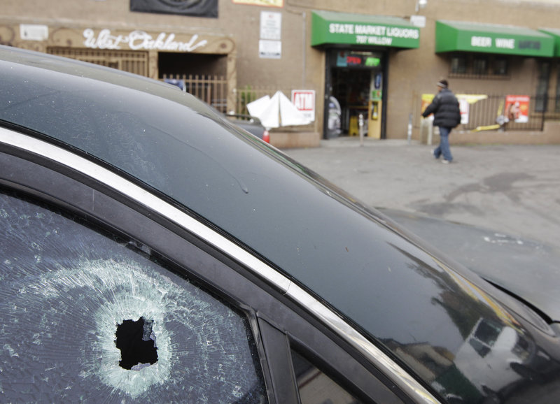 This Nov. 29, 2011, file photo shows a bullet hole in a window of a car at a liquor store parking lot in Oakland, Calif., after a shooting. A hail of gunfire along the Oakland street left eight people wounded, including a 1-year-old boy.
