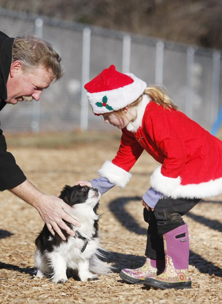 Daisy, a 6-year-old Shih Tzu mix owned by Joe Corriveau of Saco, left, gets a greeting from Parker Roenick, 5, also of Saco, at the Young School playground in Saco on Sunday.