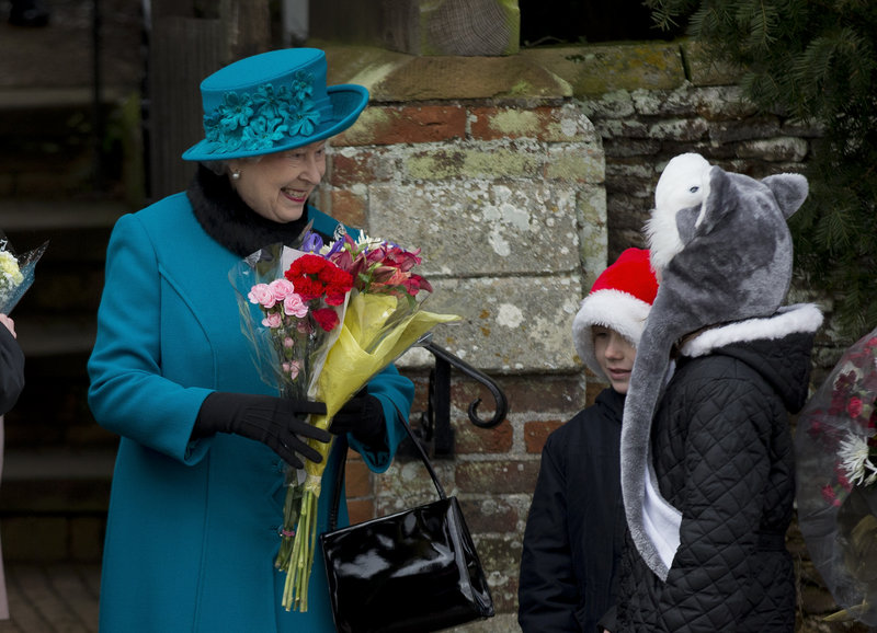 Britain's Queen Elizabeth II receives flowers from children after attending the royal family's traditional Christmas Day service in Sandringham.