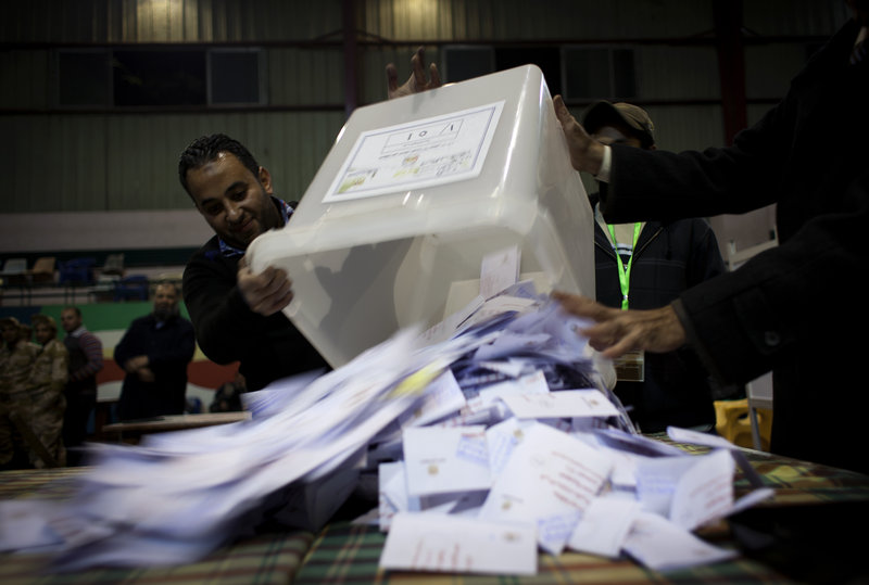 Egyptian election workers empty a ballot box for counting at the end of the second round of a referendum on a disputed constitution, at a polling station Saturday in Giza.