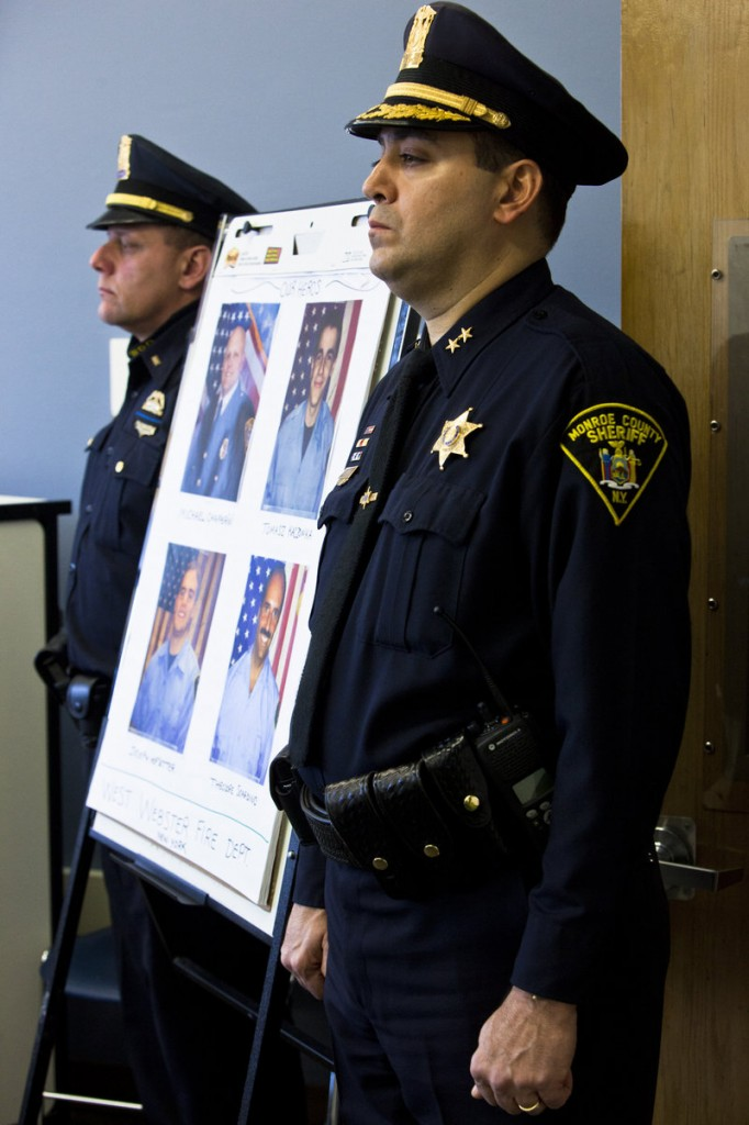 Monroe County Sheriff Deputy Chief Steve Scott, right, and Webster Police Lt. Joseph Rieger stand by a photo of the dead and wounded firefighters during a news conference in Webster, N.Y., on Christmas Day.