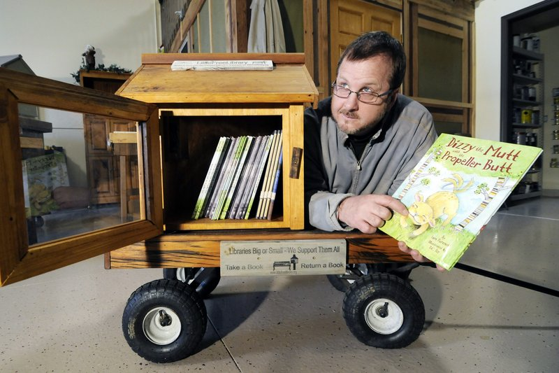 Todd Bol shows off one of the Little Free Libraries book-sharing boxes in Hudson, Wis. The nonprofit's boxes are being adopted by a growing number of groups as a way of promoting literacy in inner cities and underdeveloped countries.