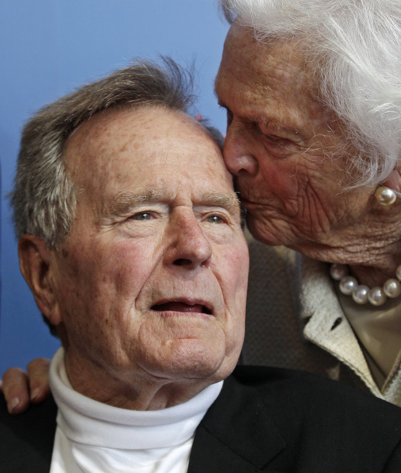 Former President George H.W. Bush gets a kiss from his wife, Barbara Bush.