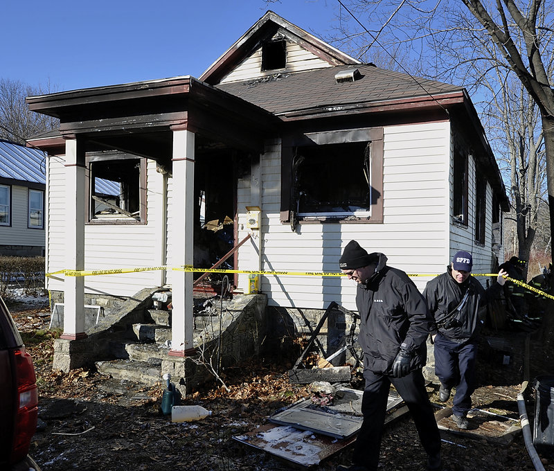 South Portland firefighters and state investigators comb through the wreckage at 15 Bodge St. in South Portland that burned in a fire on Christmas.