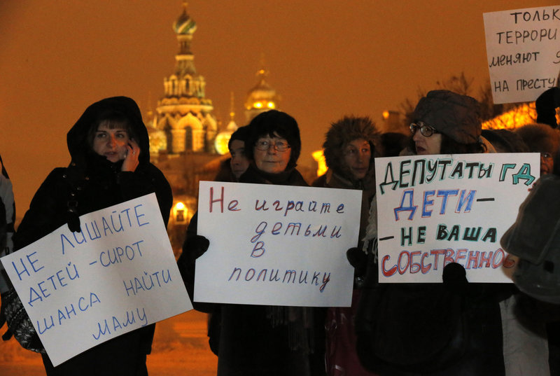 """Opposition activists hold posters reading """"Do not involve children in politics"""" and """"Lawmakers, children are not your ownership"""" during a protest Wednesday in St. Petersburg against a bill banning U.S. adoptions of Russian children."""