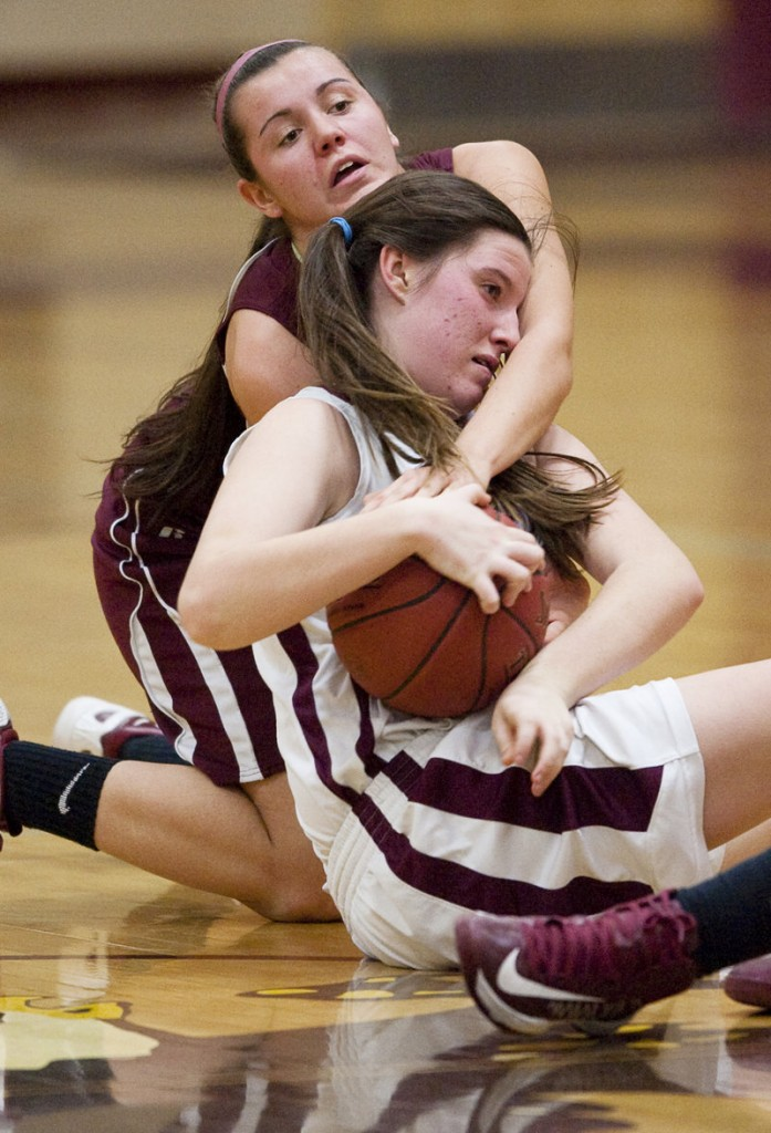 Sadie Nelson of Windham attempts to keep possession of the ball while Emily Richard of Thornton Academy seeks to force a held ball.