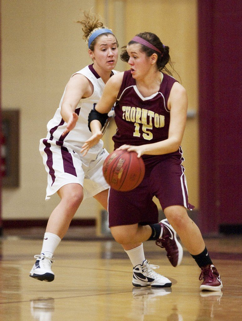 Emily Richard of Thornton Academy controls the ball and heads to the lane while looking for a way to dribble around Katie Herzig of Windham.