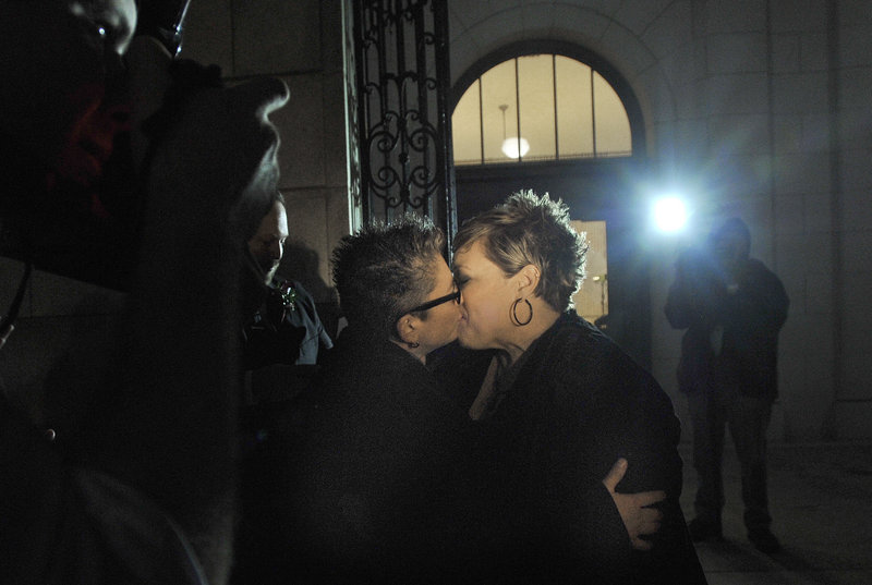 Portland newlyweds Donna Galluzzo, left, and Lisa Gorney share their first kiss as a married couple on the steps of Portland City Hall at 1:45 a.m. Saturday.