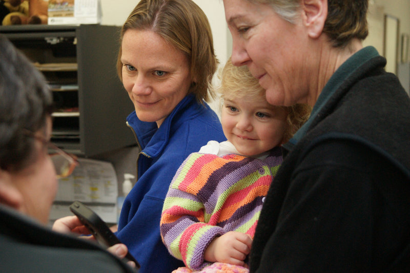Becky Roak, left, and Mary Parker get their marriage license Saturday at Brunswick Town Hall. They're accompanied by their 22-month-old daughter, Grace.