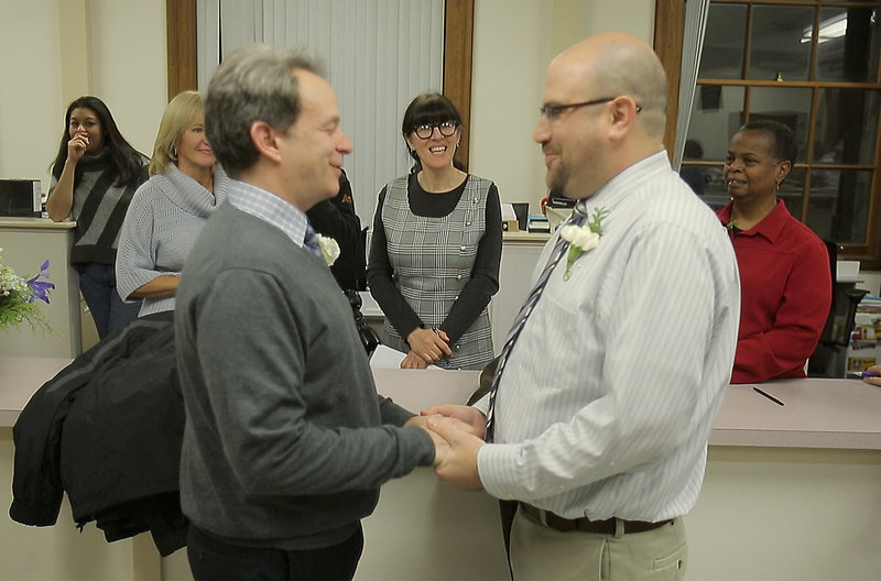 Christine Horne, center, a vital records clerk at Portland City Hall, marries Jeff Burdick, left, and Josh Laton at City Hall on Saturday.