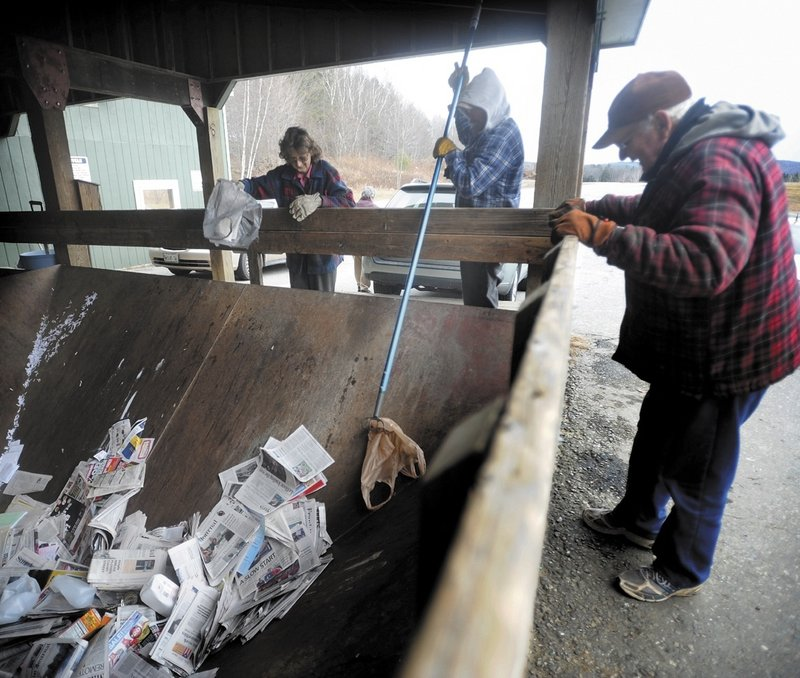Reggie Lane, center, an employee at the Wilton Transfer Station, fishes a plastic bag out of the dumpster as Lawrence Farrington, right, and his wife, Marcella, look on.