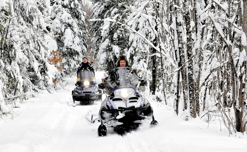 Ernie Rice, front, and Dennis Harris, both members of the Belgrade Draggin Masters club, groom snowmobile trails on Sunday. The early snow is a blessing for area snowmobilers.
