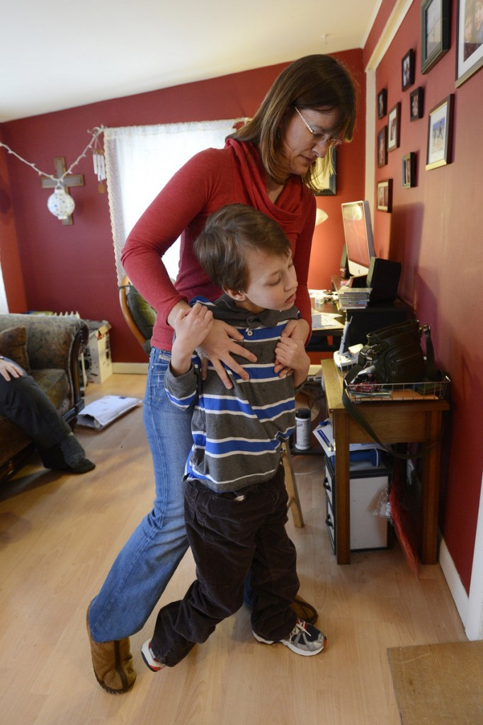 Heather Bowie helps her son Aidan, 11, walk in the family's Berwick home.