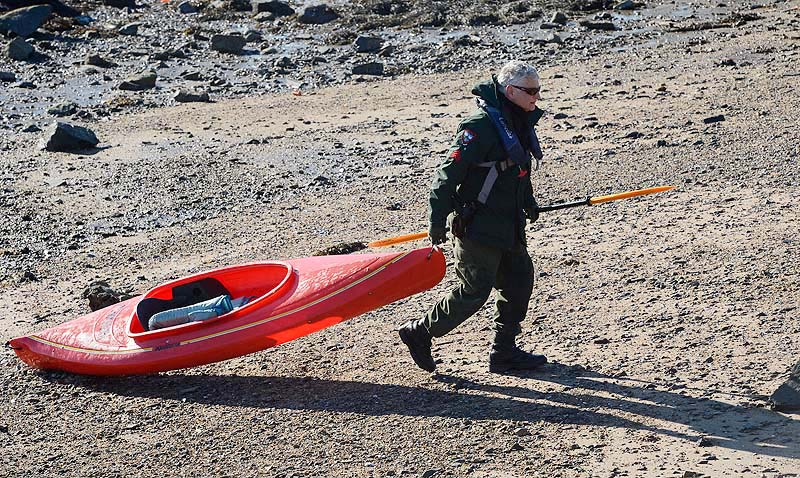 Maine Warden Service Sgt. Tim Spahr drags a kayak onto shore Monday at Cape Porpoise where the search for Zachary Wells and Prescott Wright continues.