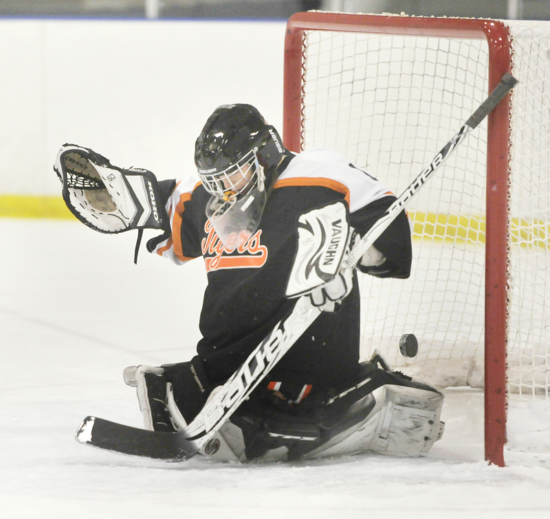 Cassie Ellis of Biddeford squeezes the goalie pads, but the puck slips through for a Cheverus goal in Wednesday's game at the Portland Ice Arena.