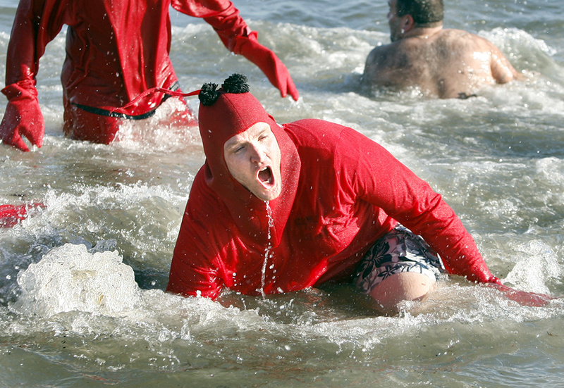 """Dave Roberts of Washington, D.C., and a member of team """"I Dip, You Dip, We Dip"""" falls into the ocean on his third dip during the 25th annual Lobster Dip to benefit Special Olympics Maine in front of The Brunswick in Old Orchard Beach on Tuesday."""