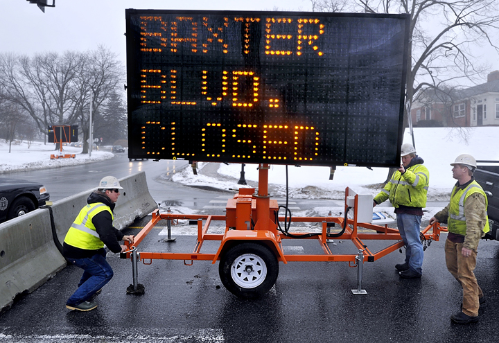 Cody Jean, foreman for the Sargent Corp., left, and his crew, Billy Ruff, program the sign message, and Seth Watts, right, sets up a flashing sign to warn motorists of the closing of Baxter Boulevard from Vannah Avenue to Bates Street until June for storm drain and holding tank replacement.