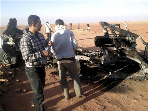 In this undated photo, men look at the wreckage of a vehicle near Ain Amenas, Algeria. Algerian bomb squads scouring a gas plant where Islamist militants took dozens of foreign workers hostage found