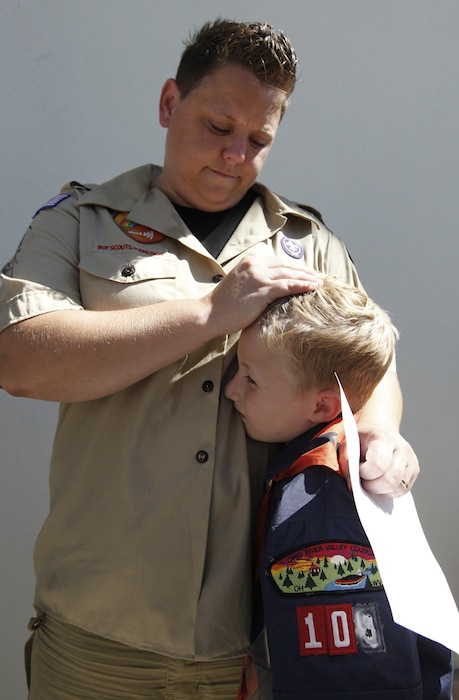 In this July 18, 2012, file photo, Jennifer Tyrrell hugs her son Cruz Burns, 7, outside Boy Scouts national offices in Irving, Texas, after a meeting with representatives of the 102-year-old organization. The Ohio woman was ousted as a den mother because she is a lesbian. The Boy Scouts of America announced Monday, Jan. 28, 2013, that it is considering a dramatic retreat from its controversial policy of excluding gays as leaders and youth members. (AP Photo/LM Otero, File)
