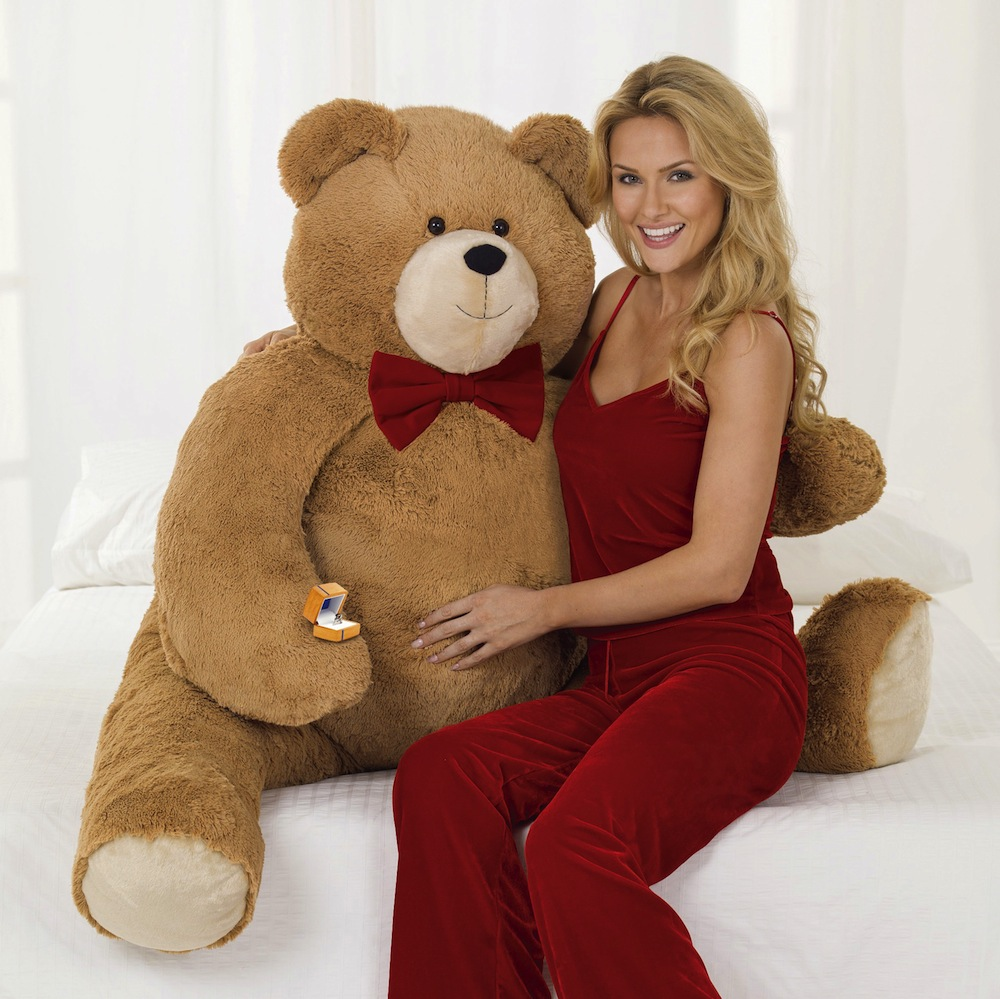 """In this photo released by Vermont Teddy Bear, a model poses with the the Big Hunka Love Diamond Bear. The Shelburne, Vt.-based company has put a $30,000 price tag on the 4½-foot-tall bear. That's because the bulk of the price is the 5.9 carat, one-of-a-kind """"fire rose"""" diamond ring made by Perrywinkle's Fine Jewelry in Burlington. (AP Photo/Vermont Teddy Bear)"""