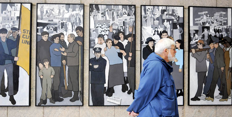 Ken Jones, of Farmingdale, on Monday examines the labor mural that is now hanging on the wall of the Cultural Building's atrium in Augusta, which serves as the entryway to the Maine State Museum.