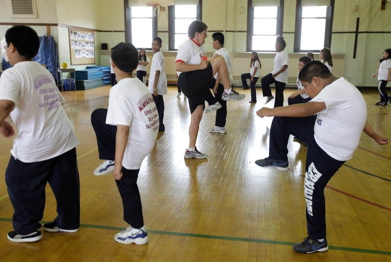 In this May 26, 2009 file photo, Betty Hale, center, instructs a physical education class at Eberhart Elementary School in Chicago. Conventional wisdom says school gym classes make a big difference in kids' weight. But a report in the New England Journal of Medicine, which goes on sale Thursday, Jan. 31, 2013, says this is one of many myths that are detracting from real solutions to the nation's weight problems. According to the report, gym classes often are not long, often or intense enough to make much difference. (AP Photo/M. Spencer Green)